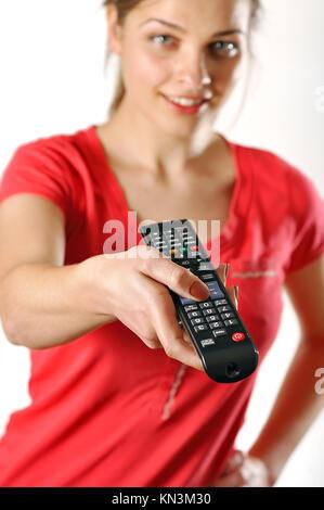 Junge Mädchen in rot Fernsehen über eine Fernbedienung. - Stockfoto