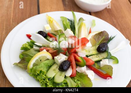 Griechischer Salat mit Feta, Tomaten, Gurken, Paprika und schwarzen Oliven. Mit Schüssel mit der Sauce auf einem - Stockfoto