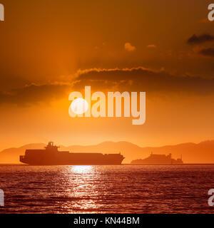 Die Insel Alcatraz Gefängnis bei Sonnenuntergang und Handelsschiff in San Francisco, Kalifornien, USA. - Stockfoto