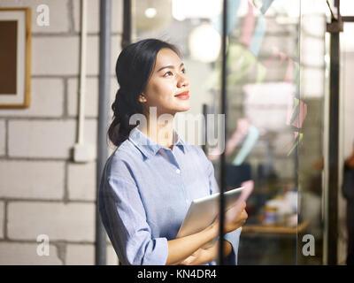 Jungen asiatischen Geschäftsfrau auf Haftnotizen auf Glas Wand während der Business Plan. - Stockfoto