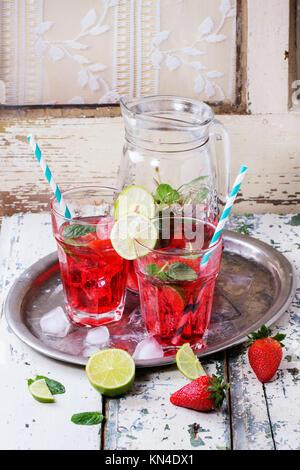 Zwei Gläser mit Retro cocktail Rohre und Glas Krug hausgemachtes Erdbeer Limonade, serviert mit frischen Erdbeeren, - Stockfoto