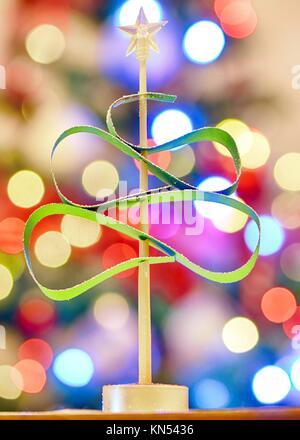 Grüner Weihnachtsbaum aus Papier über die Beleuchtung Hintergrund. - Stockfoto