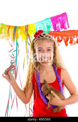 Happy Party Girl mit Welpen vorhanden Schokolade essen in Geburtstag schmutzigen Mund. - Stockfoto