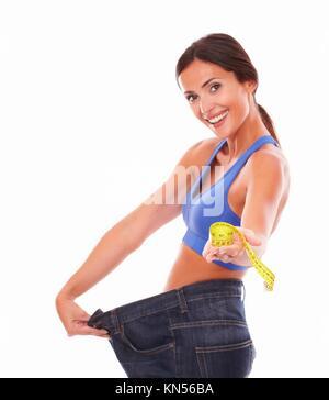 Schönen erwachsenen Dame in Sport Kleidung geben Sie Maßband, und ziehen Sie gleichzeitig Jeans auf Taille gegen - Stockfoto