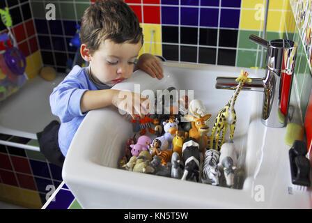 Baby Boy vier Jahre alten Spielen mit Spielzeug in einem Badezimmer, Madrid. - Stockfoto