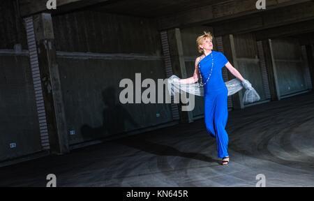 Verängstigte Frau trägt blaue Kleid im öffentlichen Parkhaus. - Stockfoto