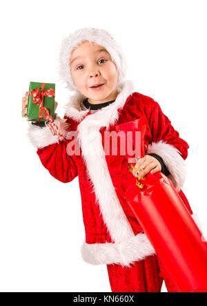 Lächelnd 5 Jahre alten Jungen tragen Santa Claus Kostüm, Weihnachtsgeschenke, weißen Hintergrund. - Stockfoto