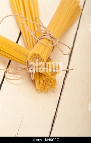 Bündel von italienischer Pasta Typ auf einem weißen rustikalen Tisch. - Stockfoto