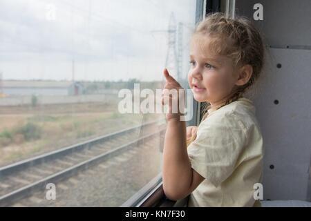 Vier Jahre Mädchen schauen aus dem Fenster mit der Unterseite des Regal in der zweiten Klasse Waggon. - Stockfoto