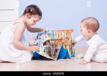 Baby Boy und Schwester spielen bei toys Zimmer mit Pop-up-Buch. - Stockfoto