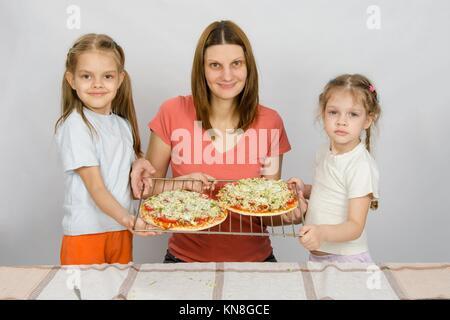 Mama und zwei kleine Töchter zeigen die beiden noch nicht gebackene Pizza auf ein Backblech. - Stockfoto