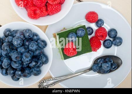 Grüner Tee Matcha mousse Torte mit Himbeeren und Blaubeeren. - Stockfoto
