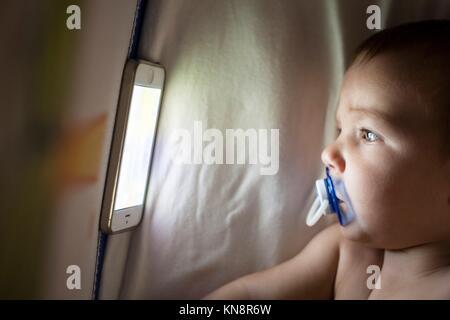 12 Monate altes Baby aufpassen ein Schlaflied cartoons mit Mobiltelefon auf die Krippe. - Stockfoto