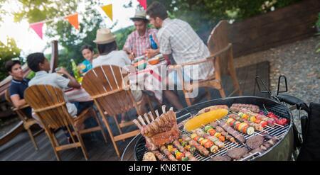 Familie mit einem Grillfest im Garten im Sommer. - Stockfoto