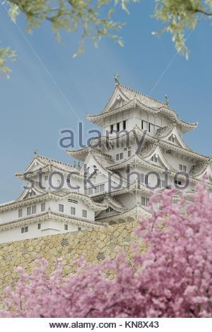 Japanische Pagode Gebäude, gesehen von einem niedrigeren Niveau, mit Pflanzen im Vordergrund. - Stockfoto