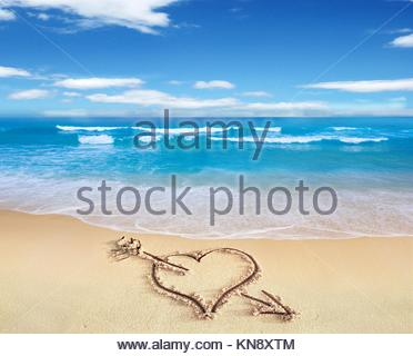 Herz mit Pfeil, als Zeichen der Liebe, direkt am Strand, mit dem Stuhl und Himmel im Hintergrund gezeichnet. - Stockfoto