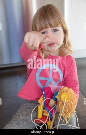 Portrait von Blond drei Jahre altes Kind mit Rosa shirt Blau Frieden hippie Symbol, sitzend auf dem Boden Küche, ärgerlichen Ausdruck, mit Marionette in