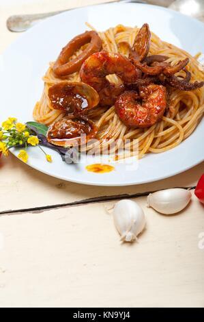 Italienisch Meeresfrüchte spaghetti Pasta auf rote Tomatensauce über Weiß rustikalen Holztisch. - Stockfoto