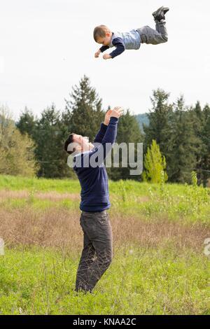 Vater warf seinen Sohn sehr hoch in der Luft, während man draußen in einem natürlichen Feld in Oregon. - Stockfoto