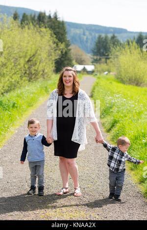 Realistische lifestyle Portrait von einer Mutter und ihren zwei Söhnen in einem Feld im Freien in Oregon. - Stockfoto
