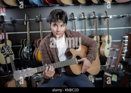 Junger Mann an der Gitarre in einem Shop, Frankreich. - Stockfoto