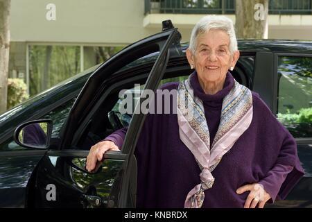 Portrait der älteren Frau mit dem Auto. - Stockfoto