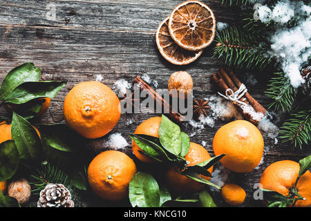 Traditionelle Weihnachten Hintergrund mit Tannenbaum, Mandarinen, Zimt und natürlichen Schnee auf Holz- Hintergrund. Ansicht von oben, getönten Bild