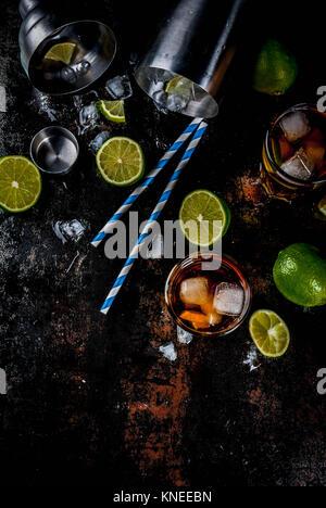Cuba Libre, Long Island oder Eistee Cocktail mit starken Alkohol, Cola, Kalk und Eis, zwei Glas, dunklen Hintergrund - Stockfoto
