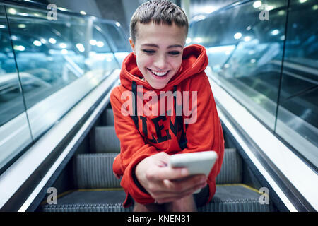 Kurze blonde junge Frau unten U-Bahnstation Rolltreppe am Smartphone suchen - Stockfoto