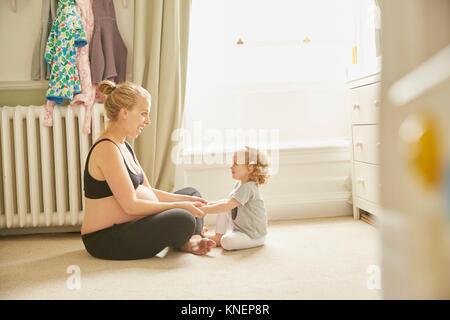 Schwangere Frau und Tochter im Schlafzimmer - Stockfoto
