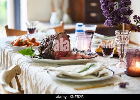 Sonntagsbraten auf Esstisch, bereit zu dienen - Stockfoto