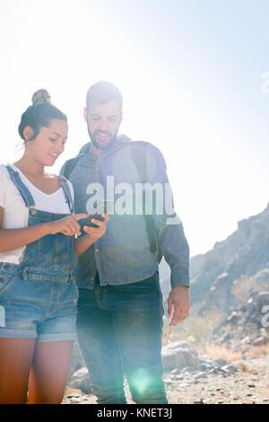 Die jungen wandern Paar an Smartphone in sonnendurchfluteten Tal suchen, Las Palmas, Kanarische Inseln, Spanien - Stockfoto