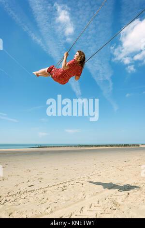 Frau auf einer Schaukel auf einem Strand, Zoutelande, Zeeland, Niederlande, Europa - Stockfoto