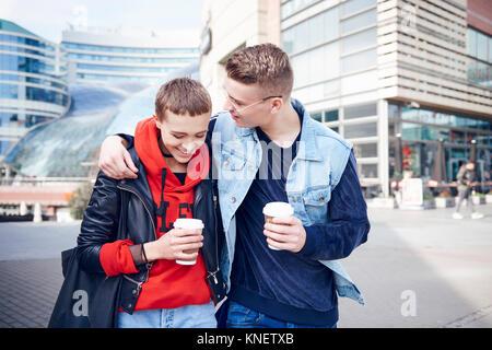 Romantische junge Paar mit Takeaway Kaffee zusammen zu Fuß in der Stadt - Stockfoto