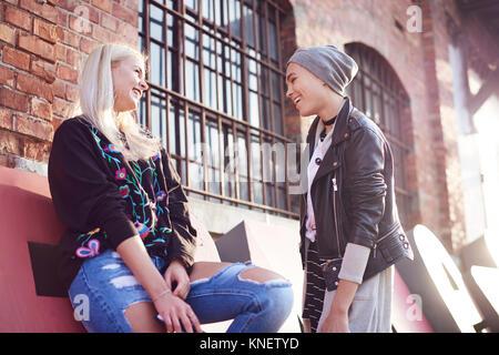Zwei junge weibliche Freunde Chatten in Stadt. - Stockfoto