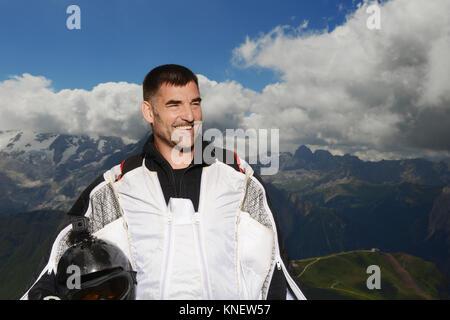 Base Jumper tragen Wingsuit weg schauen lächelnd, Dolomiten, Canazei, Trentino Alto Adige, Italien, Europa - Stockfoto