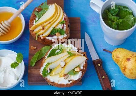 Sandwiches mit Hüttenkäse, Honig, Birne und Walnüsse mit einem Pfefferminztee. Europäische gesunde festlichen Frühstück - Stockfoto