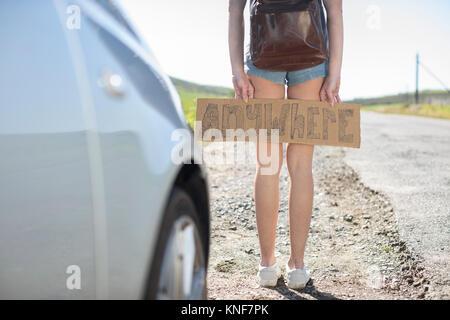 Junge Frau stand neben dem Auto, Holding trampen Schild 'Irgendwo', Abschnitt - Stockfoto
