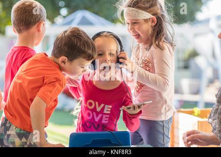 Junges Mädchen mit Freunden, Smartphone, das Tragen von Kopfhörern - Stockfoto