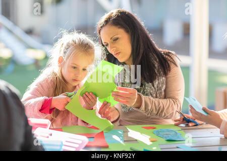 Mitte der erwachsenen Frau helfen jungen Mädchen mit Basteln Aktivität - Stockfoto
