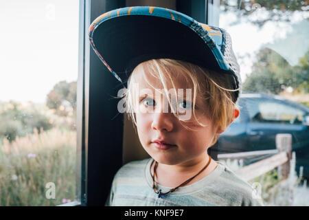 Portrait von blonder junger Mann, Baseball Cap von Fenster - Stockfoto