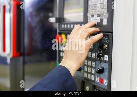 Betreiber arbeiten mit CNC-Bearbeitungszentrum über die Systemsteuerung. Selektive konzentrieren. - Stockfoto