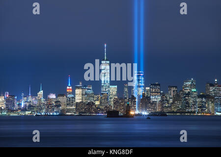 Die beiden Balken des Tribute in Light mit Wolkenkratzern von Lower Manhattan bei Nacht von New York Harbor. Financial District, New York City