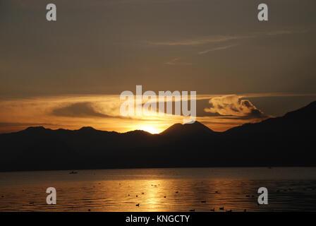 Sonnenaufgang am Lake Atitlan in Guatemala, die von hohen Klippen umgeben ist und von drei Vulkanen übersehen - Stockfoto