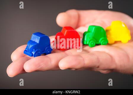 Spielzeugautos in den Farben Blau, Rot, Grün und Gelb sind auf einem Palm durchgeführt. - Stockfoto