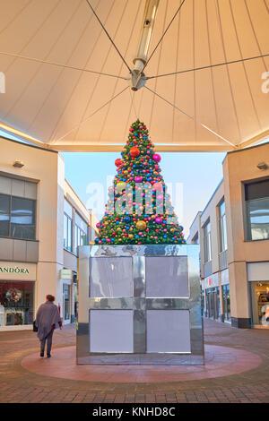 Künstlicher Weihnachtsbaum unter dem Vordach an der Willow Place Shopping Parade im Zentrum der Stadt von Corby, - Stockfoto