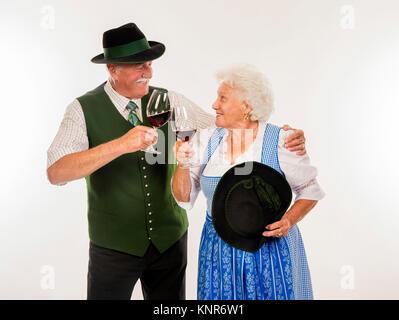 Seniorenpaar Mit Rotweinglaesern in Tracht - älteres Paar in Tracht - Stockfoto