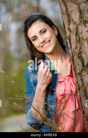 Junge Frau Steht Neben Baumstamm - steht Frau neben Baumstamm - Stockfoto