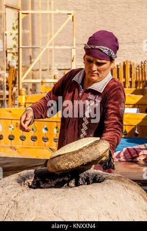 Eine lokale Frau backt Brot in einem traditionellen Lehmofen, Chiwa, Usbekistan - Stockfoto