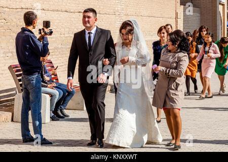 Eine junge USBEKISCHE Paar zu Fuß durch die Straßen von Chiwa nach der Hochzeit, Chiwa, Usbekistan - Stockfoto
